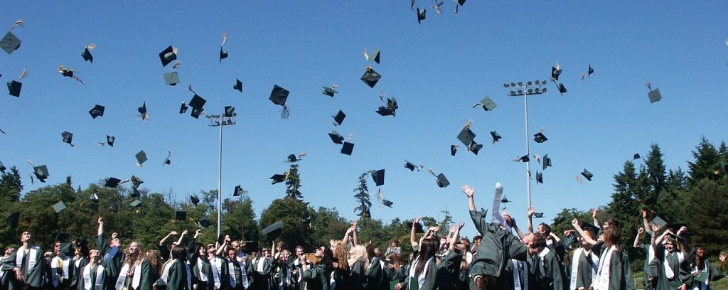 Graduating students throwing their caps in the air.