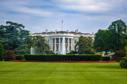 Photo of the outside of the White House on a sunny day.