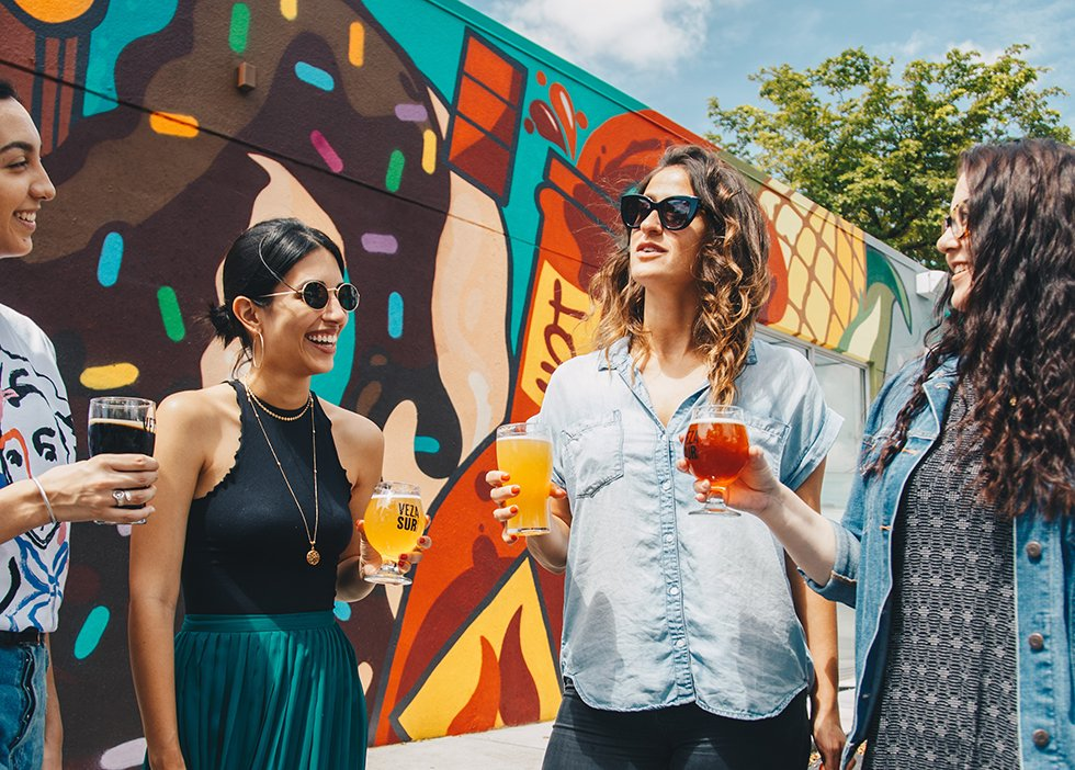 Friends drink beer in the sun in front of a wall of graffiti.