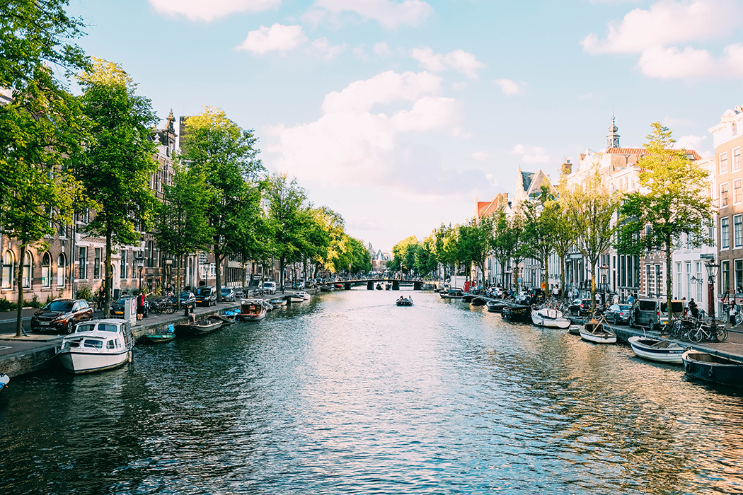 Picture of a canal in Amsterdam on a sunny day lined with small boats.