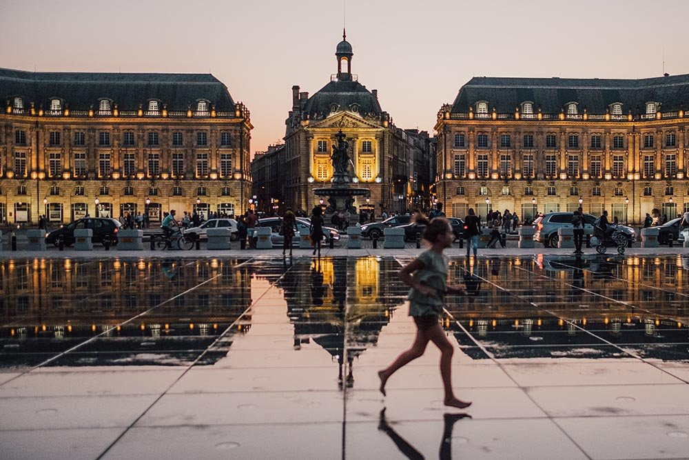 Photo of a girl running through a public square in Bordeaux.
