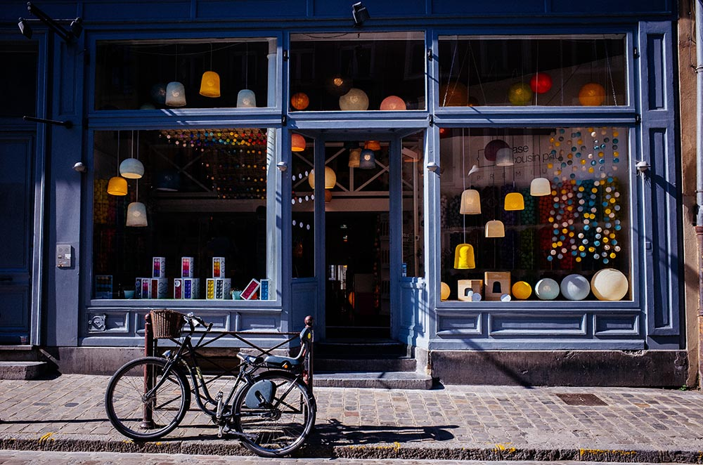 Photo of a bike in front of a cute shop in Lille, France.