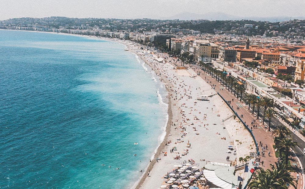 Photo of a crowded beach on a sunny day in Nice.