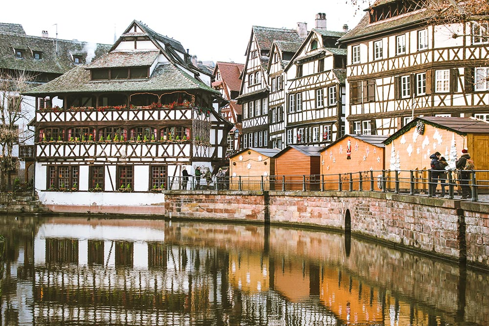 Photo of a canal in Strasbourg, with some buildings that show French/German influence.