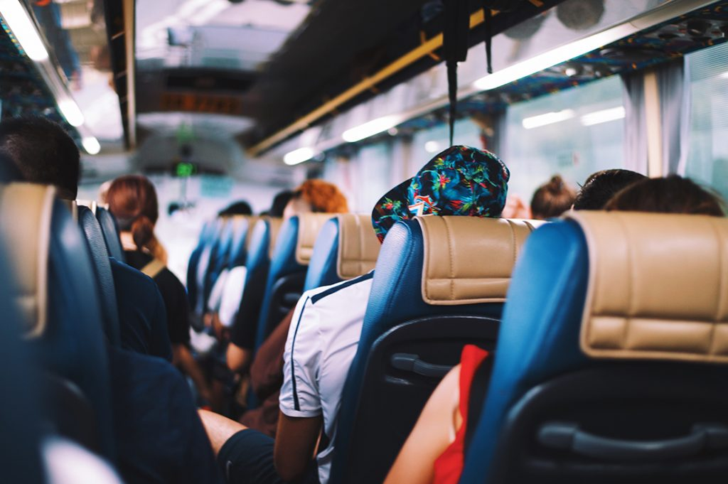 Photo of people seated on a bus.