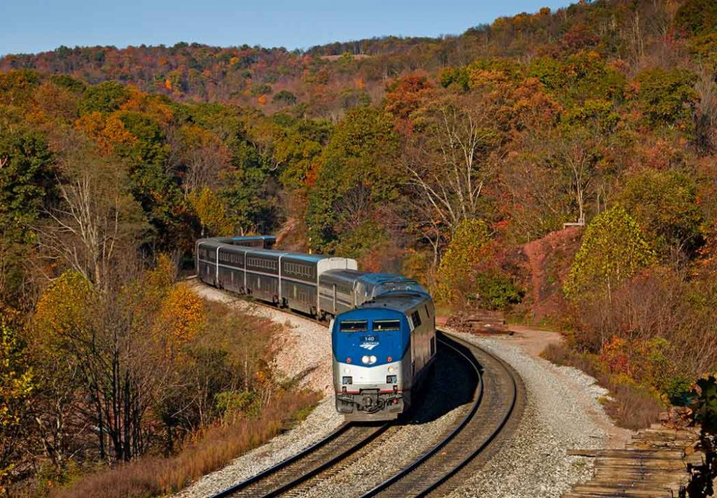An Amtrak train weaves through fall foliage in New England.