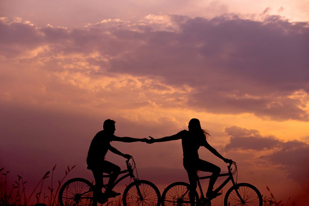 A couple in a long-distance relationship go on a bike ride at sunset.