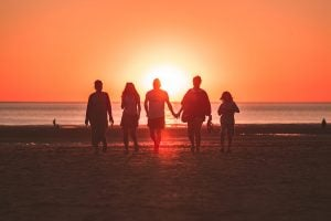 Photo of a family on the beach at sunset.