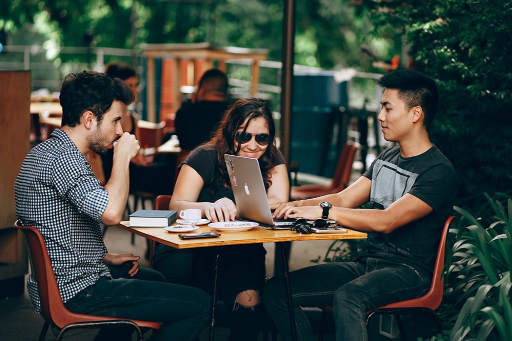 A group of millennials sit around in a coffee shop while on vacation.