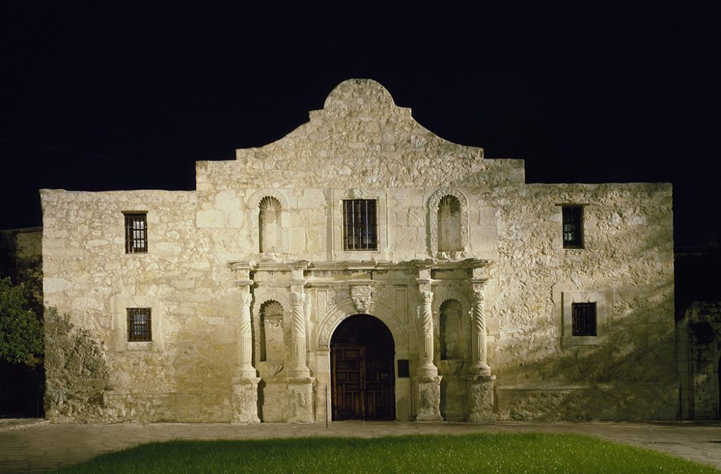 Photo of the famous Alamo mission at night.