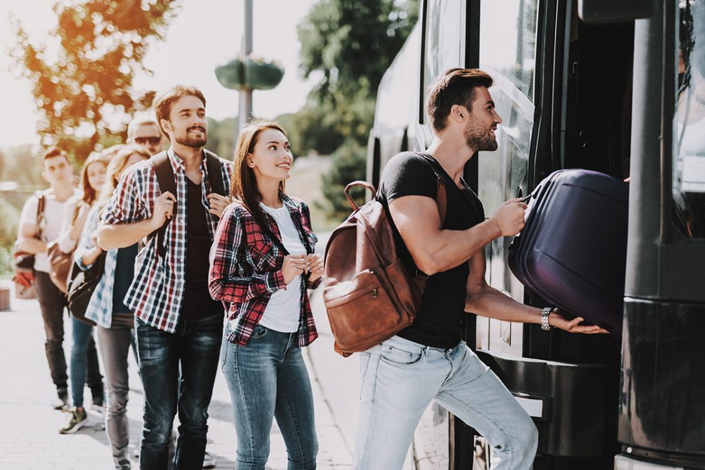 A group of travelers with trip protection board a bus.