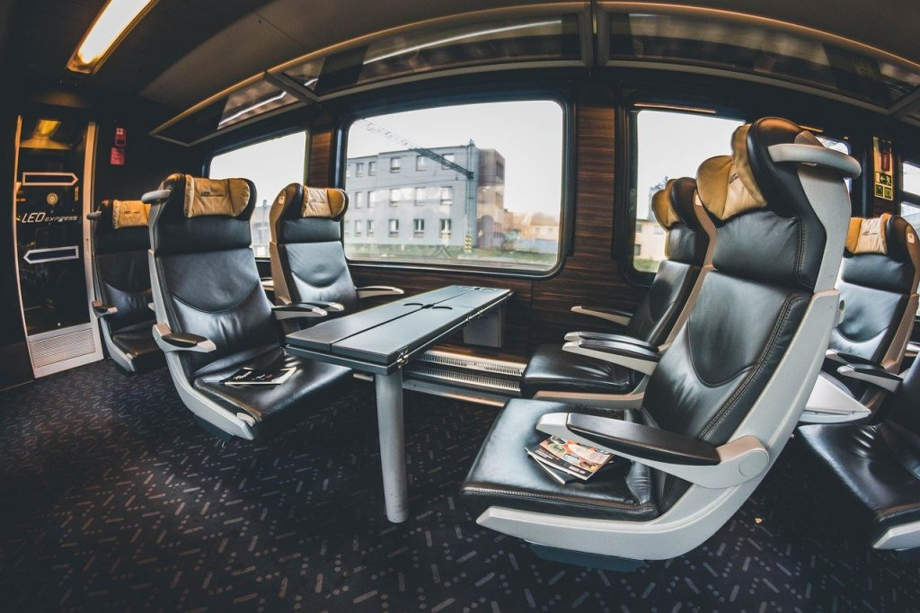Photo inside a train that's filled with amenities like leather seats and extra legroom.
