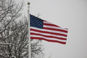 Photo of the American flag on a snowy day in February.