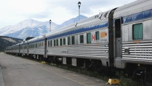 A VIA Rail train pulls into the station with mountains in the background