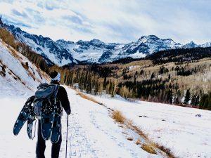 A snowshoer gazes upon snowy mountains in Colorado