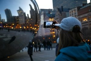 A traveler snaps a photo of Chicago's Cloud Gate