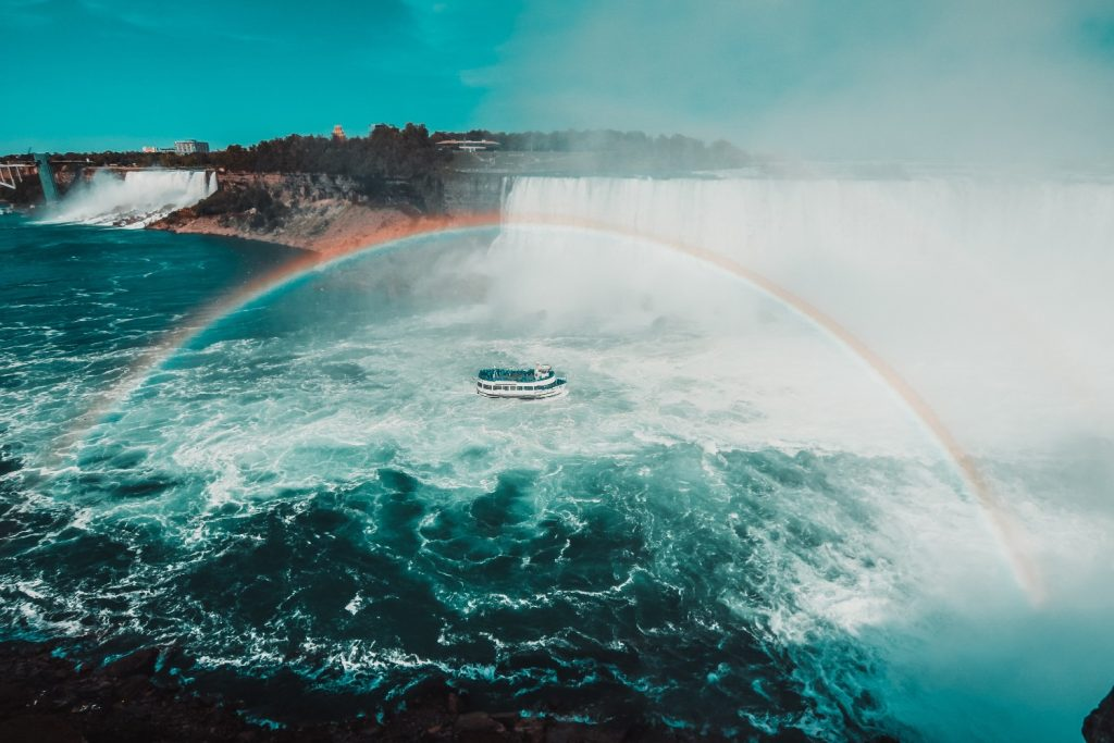A rainbow forms over the Maid of the Mist boat