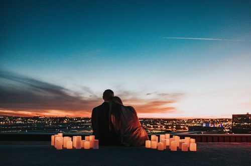 A couple gazing out at a beautiful sunset.
