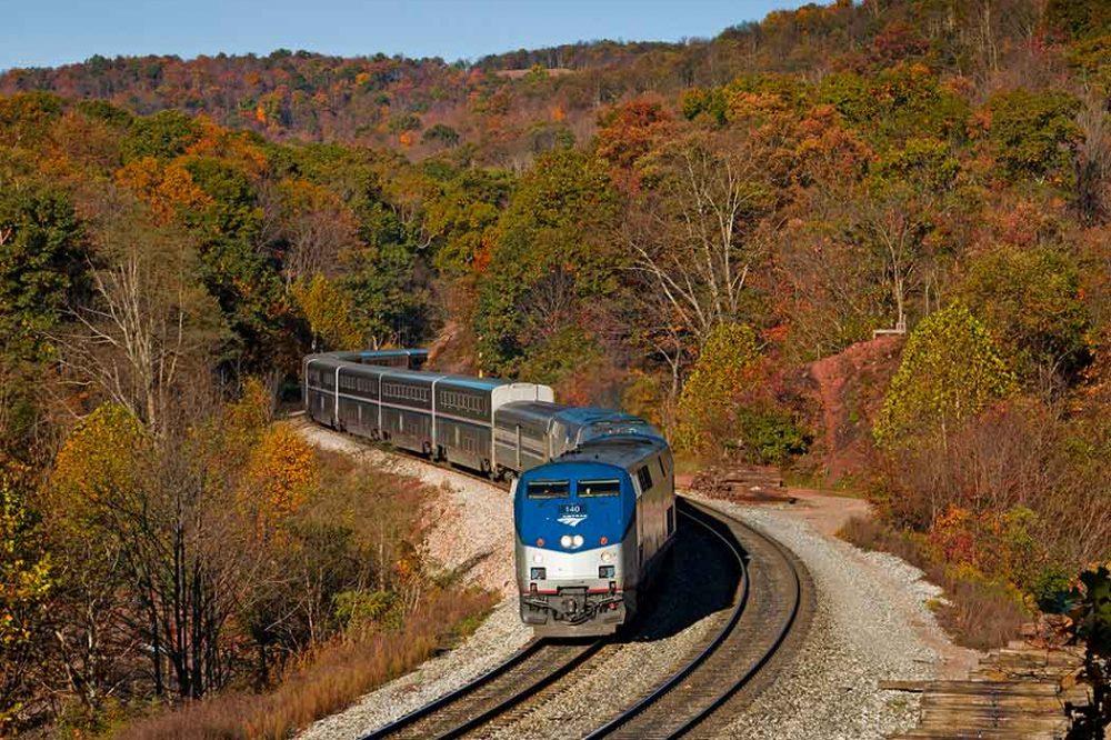 An Amtrak train weaves through fall foliage in New England.