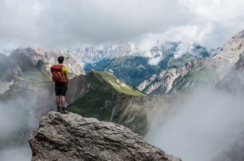 Photo of a hiker looking out at a beautiful mountain range.