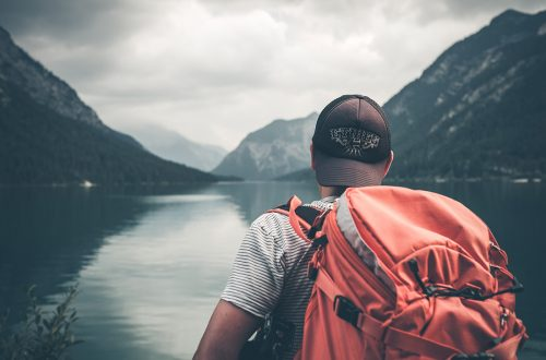 Solo traveler gazing out at a lake.